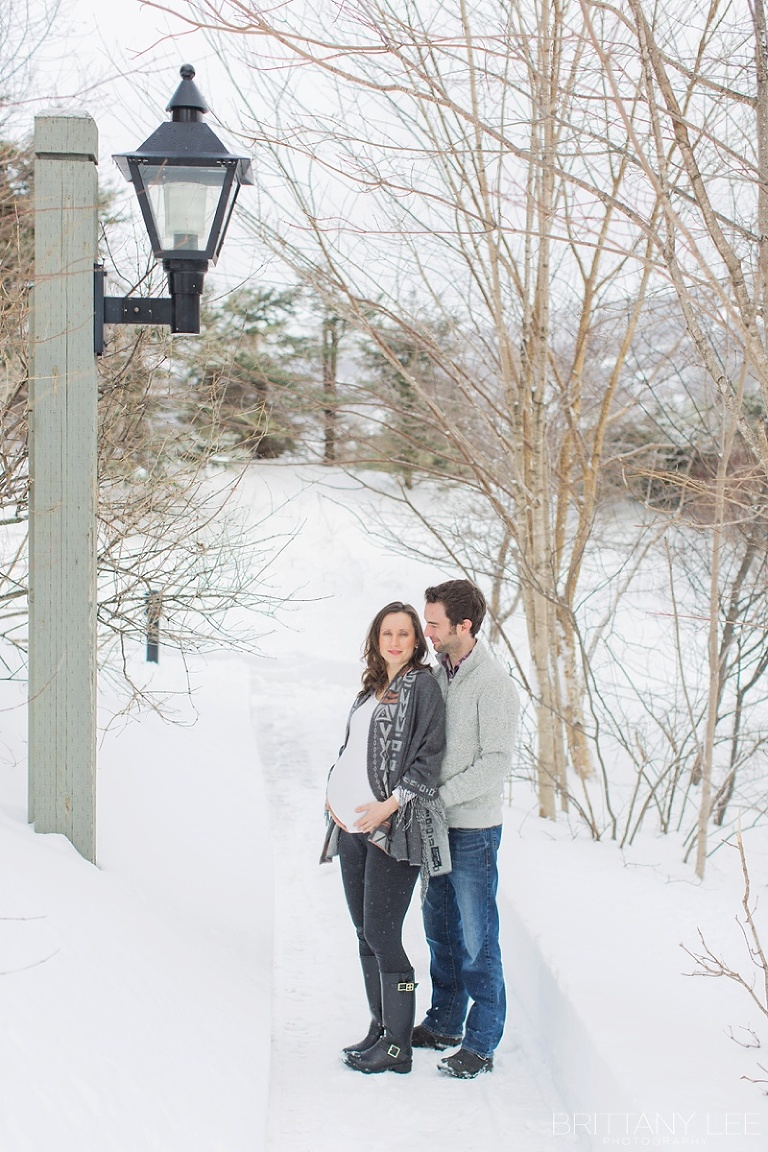 Mont Tremblant Winter Maternity Photos - couple standing on snow covered path way